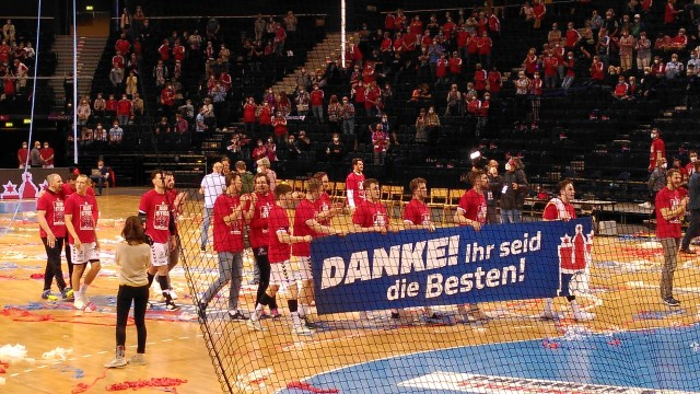 Handballmannschaft mit Dankesbanner auf dem Feld