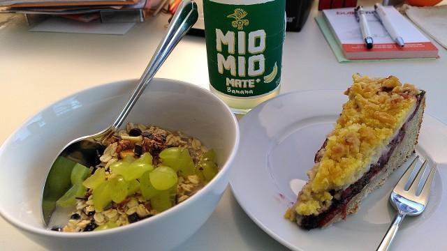 Müslischale mit Müsli mit frischen Trauben, Pflaumenkuchen und Mio Mio Mate Banane