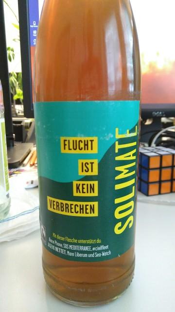 """Eine Flasche Solimate mit Aufdruck """"Flucht ist kein Verbrechen"""""""