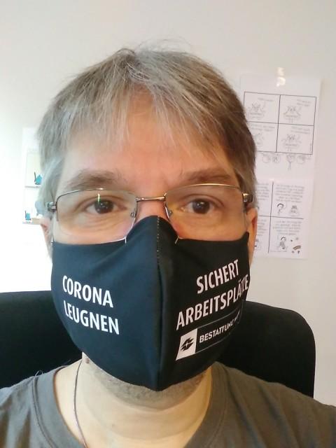 """Mundnasenschutz mit Aufschrift """"Corona leugnen sichert Arbeitsplätze"""" von den Wienern Bestattern."""