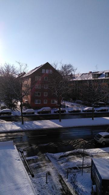 Straße mit verschneiten Wegen, die Fahrspuren sind frei