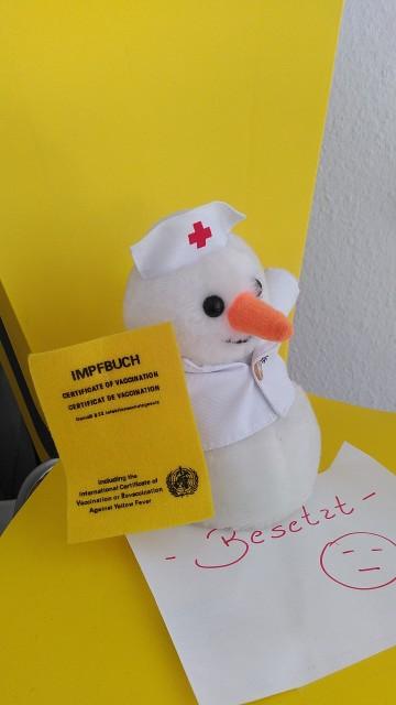 Plüschfigur mit Krankenschwesterhaube und Impfpass in der Hand auf einen Stuhl.