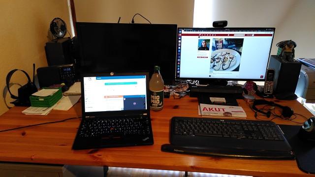 Schreibtisch mit Notebook (auf dem läuft der Stream) und daneben großem Bildschirm (mit Friendica), dazu eine Flasche Mate.