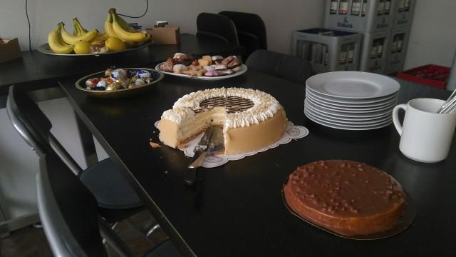 im Vordergrund zwei Kuchen, dahinter Kekse und Weihnachtssüßigkeiten, dahinter Obst.