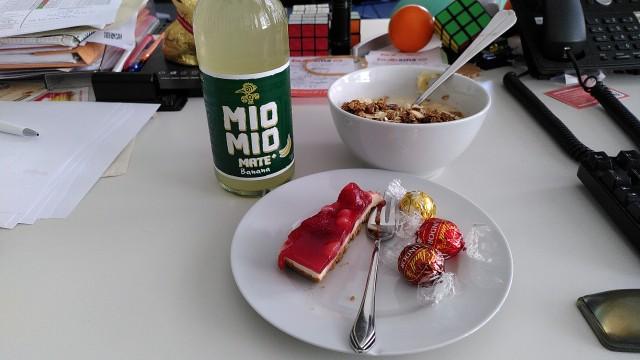 Mio-Mio-Mate Banane, Müslischale mit Müsli und Kuchenteller mit Erdbeerkuchen und Schokoladenkugeln