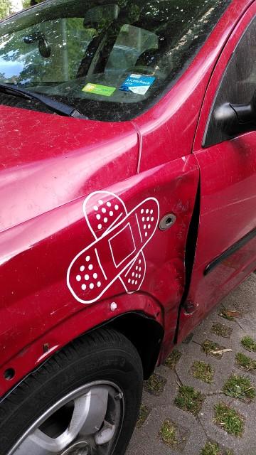 Fahrzeug mit Delle an der Seite, auf der ein Aufkleber mit einem Pflaster klebt.
