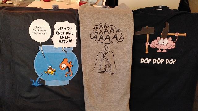 """Drei T-Shirts. Ein Hirn, das mit Hämmern auf sich einschlägt, ein Insekt, das """"aaaaah"""" schreit und zwei Fische im Aquarium. Der kleine Fisch sieht wie Greta Thunberg aus und weißt auf ein Loch im Aquarium hin, der große Fisch meint, dass der kleine Fisch erst mal den Dreisatz lernen solle."""