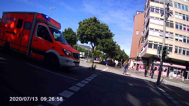 Querendes Rettungsfahrzeug, im Hintergrund zwei Radfahrer, die gerade die Straße überquert hatten