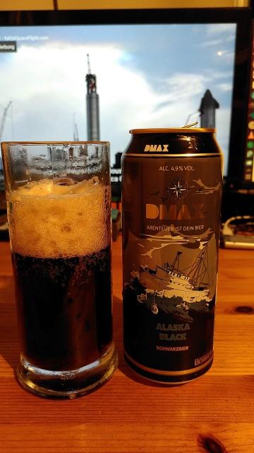 Dose Schwarzbier neben gefüllten Glas