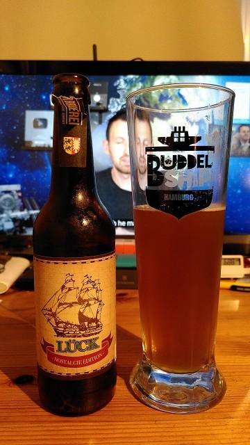 """Bierflasche mit gefüllten Bierglas. Das Bier trägt den Namen """"Lück""""."""