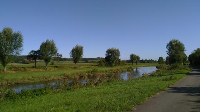 Bach mit grünen Feldern und wolkenloser Himmel
