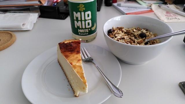 Eine Flasche Mate, eine Schüssel Müsli und ein Teller mit Kuchen auf Schreibtisch
