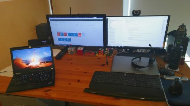 Schreibtisch mit zwei Monitoren und einem Notebook mit dem SpaceX-Livestream