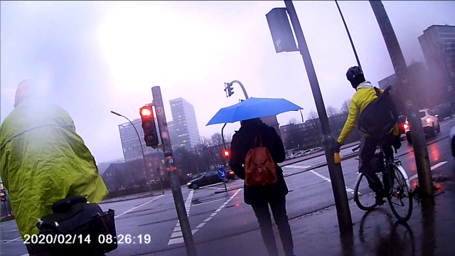 Ampelkreuzung mit zwei Radfahrern und einem Fußgänger. Einer der Radfahrer steht so, dass er das Fahrradsignal nicht sehen kann und schaut auf das Fußgängersignal
