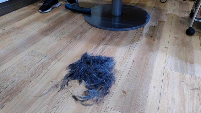 Zusammengefegte Haare vor einem Friseurstuhl