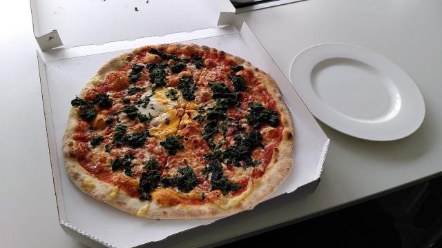 Sehr große Pizza neben einem normal großem Teller