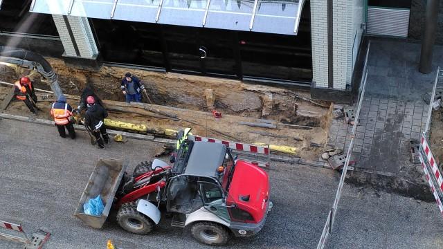 Erdarbeiten direkt an einer Hauswand. Man sieht im Fundament gemauerte Reste von seitlich abzweigenden Wänden.