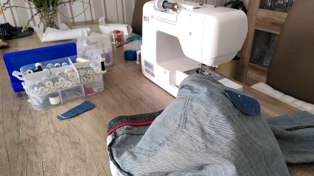 Hose mit Flicken, im Hintergrund eine Nähmaschine und Schneidereibedarf