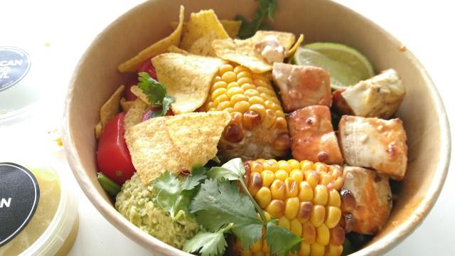 Bowl mit Mais, Tacos, schwarze Bohnen, Tofu, Tomaten ...