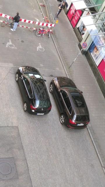 zwei Autos vor Behindertenparkplätzen im Wendehammer