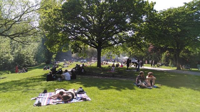 Eilbekpark mit vielen Menschen, die auf der Wiese sitzen.