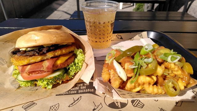 Burger mit viel Belag und eine Portion Pommes mit Chilischoten, Zwiebeln, Frühlingszwiebeln und Erdnusssauce