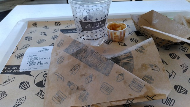 Tablett mit leeren Becher, leerem Soßenbecher und Papier, in das ein Burger eingepackt war