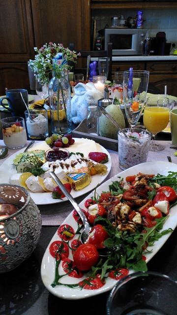 Österlich dekorierter Tisch mit Antipasti, Käse, Orangensaft.