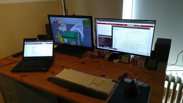 Schreibtisch mit Notebook und zwei Bildschirmen.