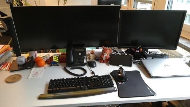 Schreibtisch mit Monitor im Breitbildformat und daneben ein normaler Monitor