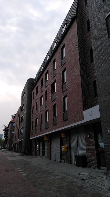 Roter Backstein-Neubau, im Hintergrund ein Backstein-Altbau