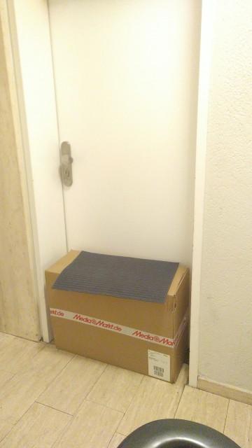 großes Paket unter einer Fußmatte in der Wohnungstür