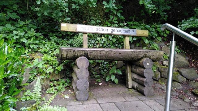 Holzbank mit dieser Aufschrift, auf der man seine Beine baumeln kann.