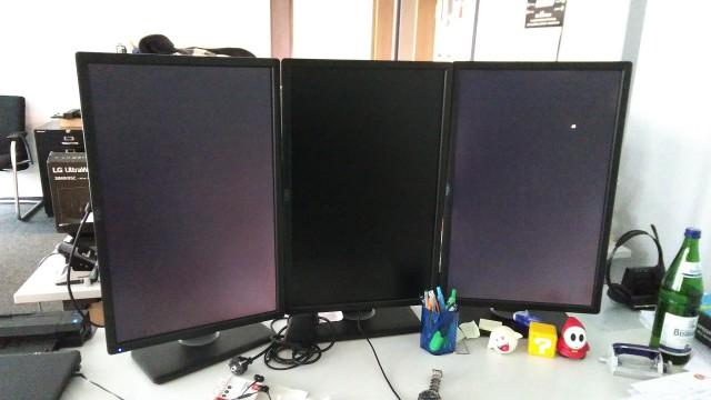 Drei hochkant aufgestellte Bildschirme