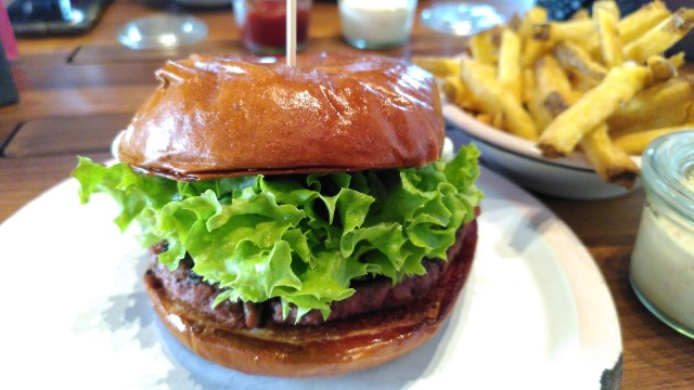 Vegetarischer Burger mit frischem Salatblatt auf Teller, im Hintergrund eine Portion Pommes.