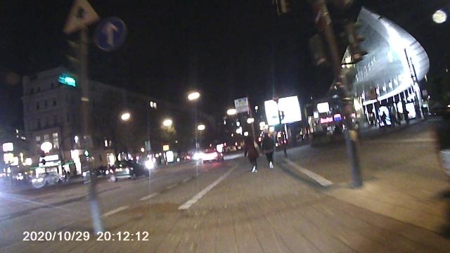 Zwei Fußgänger überqueren nebeneinander die Straße auf der Radspur