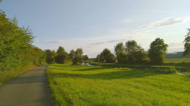 Bach und grüne Wiesen im Sonnenuntergang