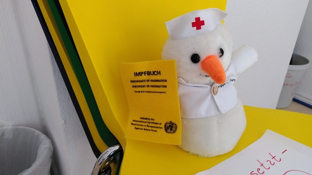 An einen Schneemann erinnernde Plüschfigur in Krankenschwesterkleidung mit Impfbuch in der Hand auf einem Stuhl im Wartezimmer