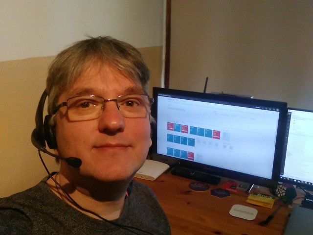 Selfie mit Headset vor Schreibtisch mit zwei Monitoren