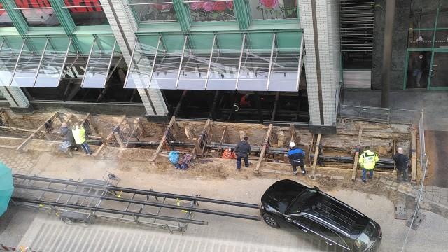 Baustelle zur Rohrverlegung mit langem Graben. Zwei Leute im Graben, 6 Leute schauen augenscheinlich von außen zu.