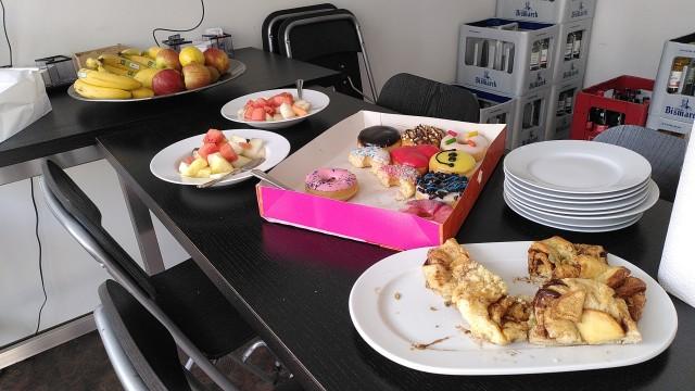 Tisch mit Donuts, Franzbrötchen und Obst.