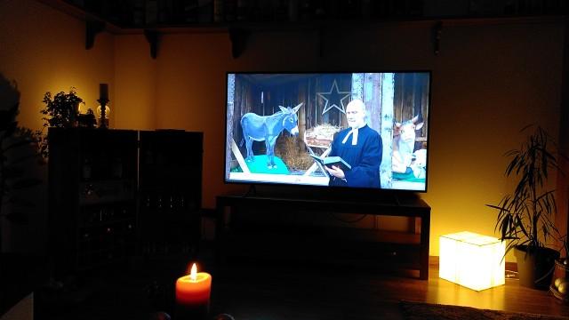 Wohnzimmer mit Fernseher im Hintergrund, auf dem derzeit der Gottesdienst läuft.